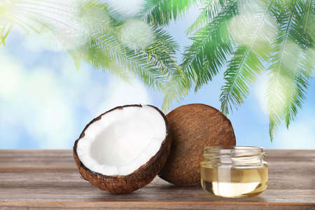 Coconuts and natural organic oil on wooden table against tropical palm leaves 스톡 콘텐츠
