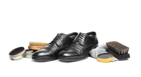 Stylish mens footwear and shoe care accessories on white background