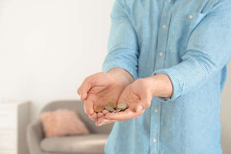Man holding coins in hands indoors, closeup. Space for text Zdjęcie Seryjne - 125165719