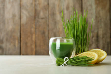 Glass of wheat grass juice with citrus fruit and sprouts on table. Space for text