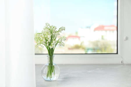 Beautiful lily of the valley bouquet in vase on windowsill, space for text