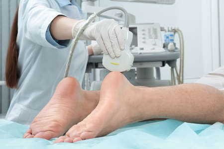 Doctor conducting ultrasound examination of patient's foot in clinic Stock Photo