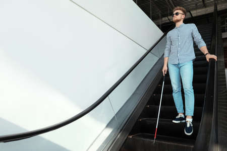 Blind person with long cane on escalator indoors. Space for text