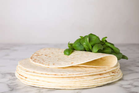 Stack of tasty tortillas with basil leaves on marble table. Space for text