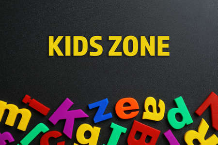 Phrase KIDS ZONE made of plastic magnetic letters on black background, top view