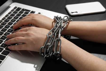 Mujer con manos encadenadas usando laptop sobre fondo negro, primer plano. Concepto de soledad