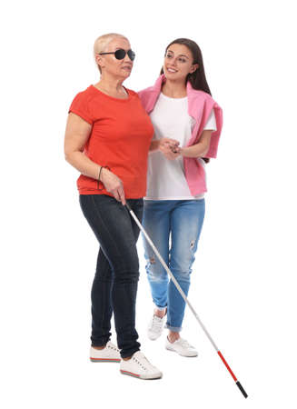 Young woman helping blind person with long cane on white background