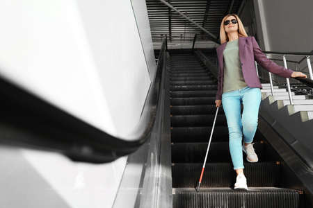 Blind person with long cane on escalator indoors