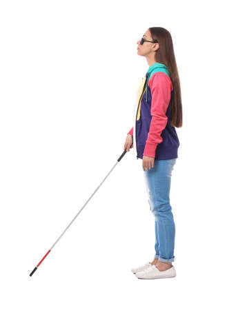 Young blind person with long cane walking on white background Stock Photo
