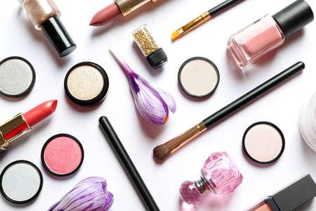 Diferentes productos de maquillaje y flores sobre fondo blanco, vista superior
