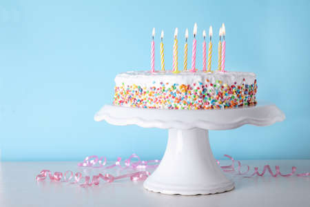 Birthday cake with burning candles on table against color background. Space for text