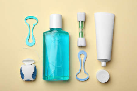 Flat lay composition with tongue cleaners and teeth care products on color background