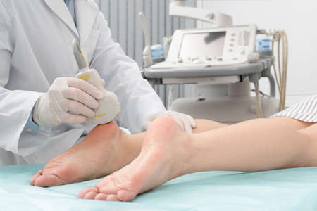 Doctor conducting ultrasound examination of patients foot in clinic, closeup