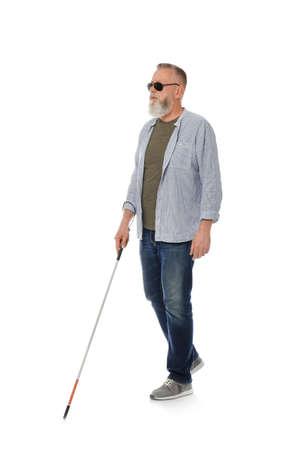 Ciego maduro con bastón largo caminando sobre fondo blanco. Foto de archivo