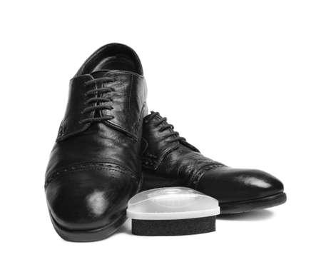 Stylish men's shoes and polishing sponge on white background