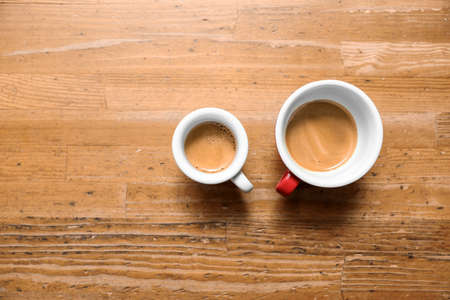 Cups of fresh coffee on wooden table, flat lay. Space for text Zdjęcie Seryjne - 125166376