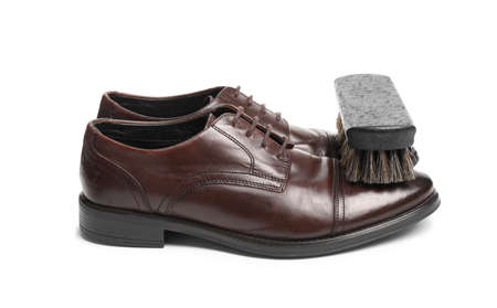 Stylish men's shoes and cleaning brush on white background