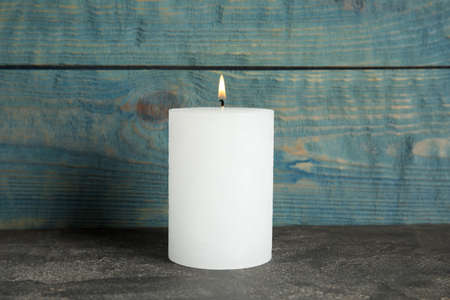 Alight wax candle on table against wooden background