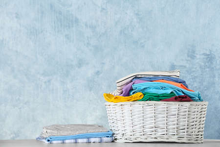 Basket with clean laundry on table against color background, space for text
