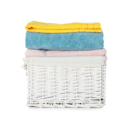 Folded towels in wicker basket on white background. Laundry day