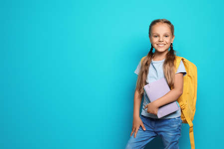 Little school child with backpack and copybook on color background 스톡 콘텐츠
