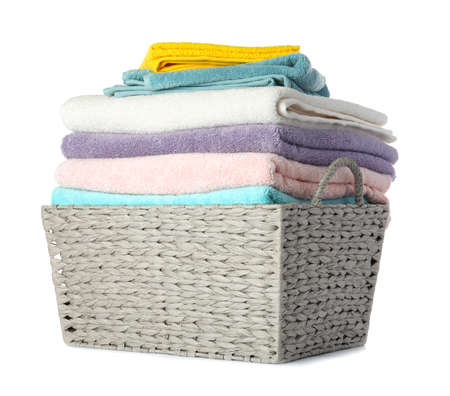 Wicker laundry basket with clean towels on white background Imagens