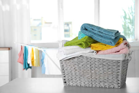 Basket with clean laundry on table at home, space for text