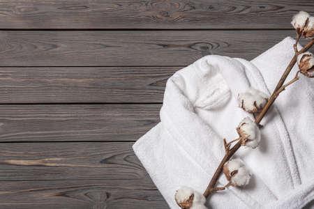 Composición plana con albornoz doblado y flores de algodón sobre fondo de madera, espacio para texto Foto de archivo