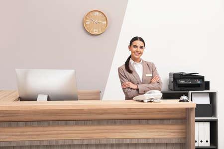 Porträt der Empfangsdame am Schreibtisch im modernen Hotel? Standard-Bild