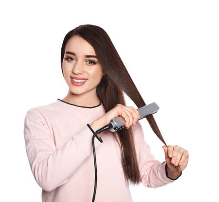 Happy woman using hair iron on white background