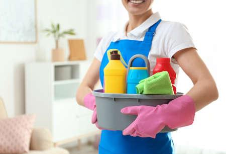 Frau mit Waschmittelwaschbecken im Wohnzimmer, Nahaufnahme. Reinigungsservice