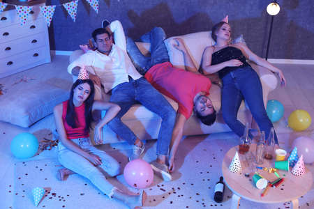 Group of friends sleeping in messy room after party at night