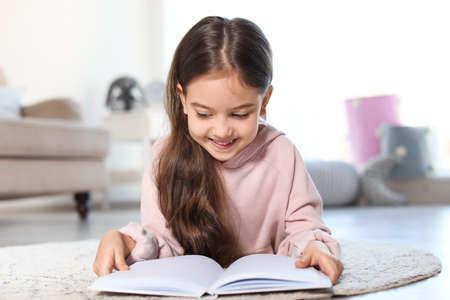 Libro de lectura de niño lindo en el piso en el interior Foto de archivo