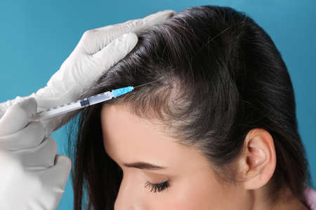 Young woman with hair loss problem receiving injection on color background, closeup