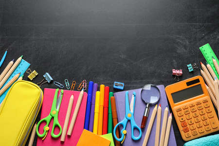 Flat lay composition with scissors and school supplies on dark background. Space for text Standard-Bild