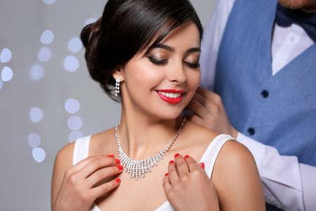 Man putting elegant jewelry on beautiful woman against blurred background Foto de archivo