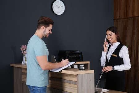 Client registering at desk while receptionist talking on phone in lobby