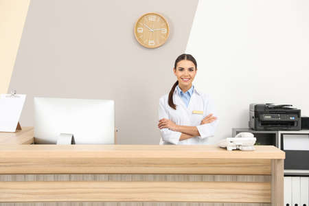 Portrait of receptionist at desk in modern clinic