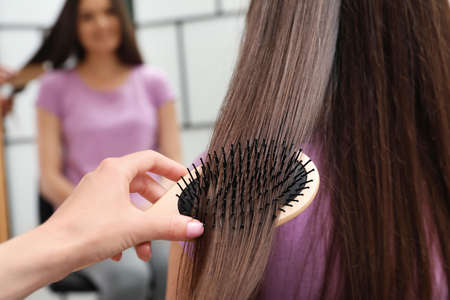 Woman combing friend's hair with cushion brush indoors, closeup