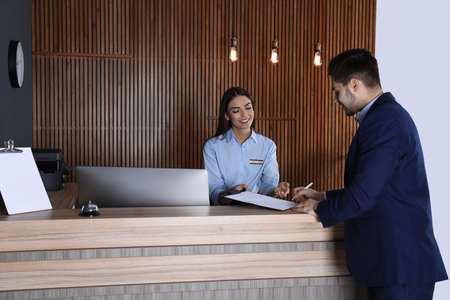 Recepcionista registrando al cliente en el escritorio en el vestíbulo Foto de archivo