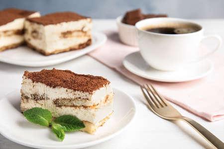 Tiramisu cake and drink served on table