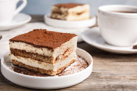 Composition with tiramisu cake and tea on table, closeup. Space for text Imagens