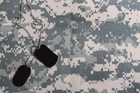 Military ID tags on camouflage background, top view. Space for text