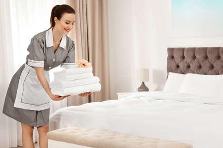 Camarera poniendo toallas limpias en la cama en la habitación del hotel. Espacio para texto Foto de archivo