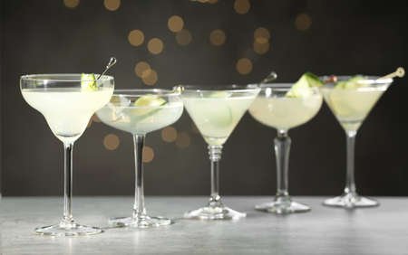 Glasses of martini with cucumber on grey table against blurred lights