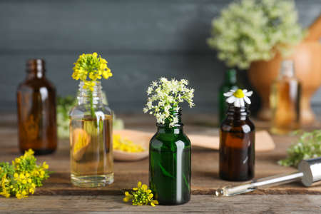 Bottles of essential oils, pipette and flowers on wooden table