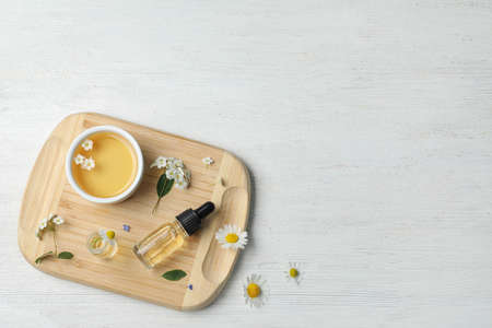 Flat lay composition with essential oil and flowers on white wooden table, space for text