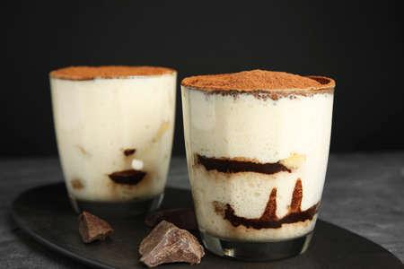 Two glasses of tiramisu cake on table against dark background, closeup