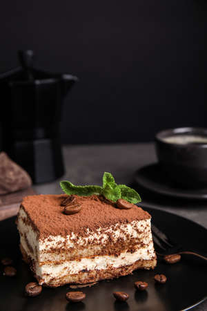 Composition with tiramisu cake on table against dark background