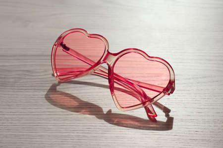 Stylish heart shaped sunglasses on wooden background Stock Photo